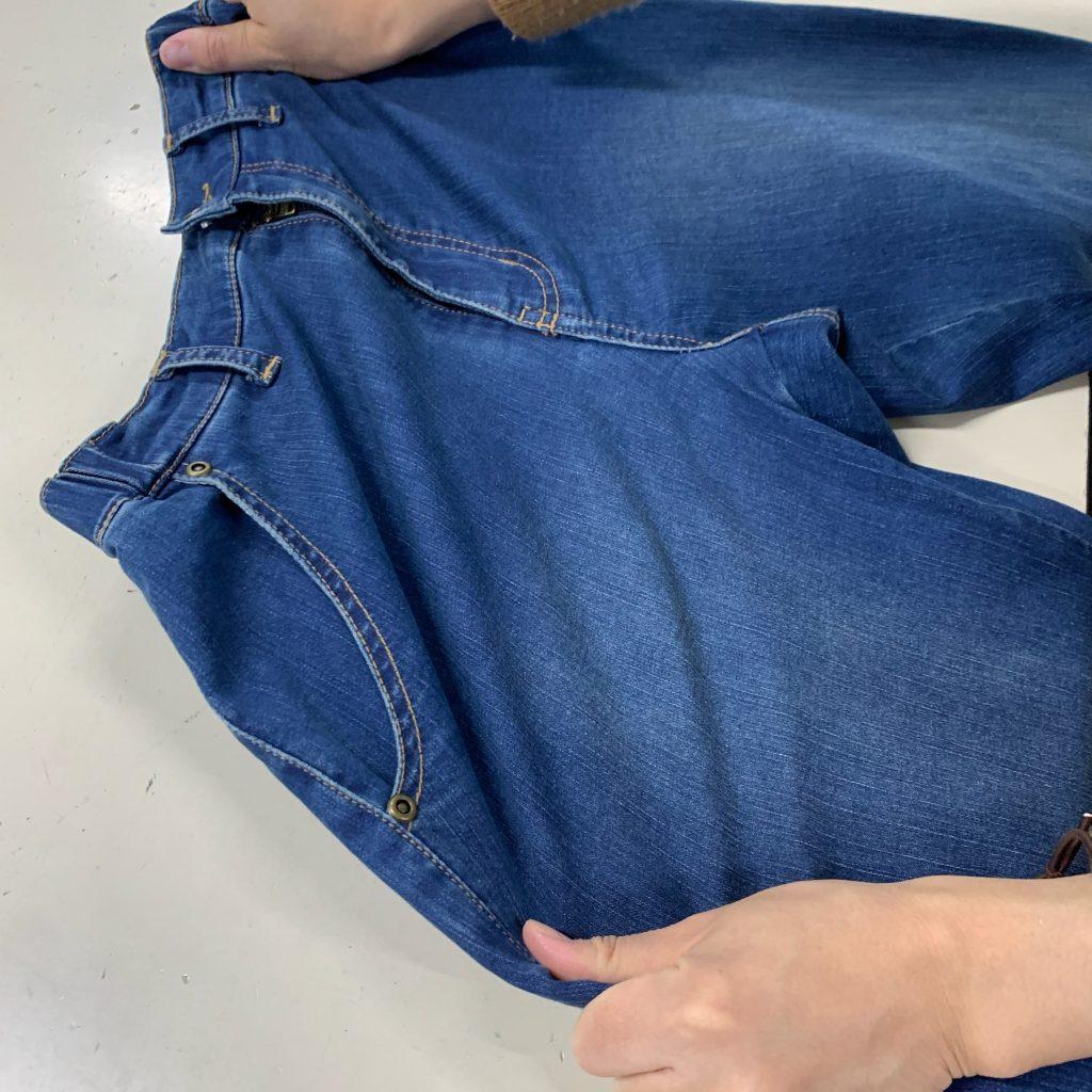 岡山地域のデニムを使ったジーンズがよく伸びる様子を撮った写真。両手でジーンズを左右に伸ばしている。