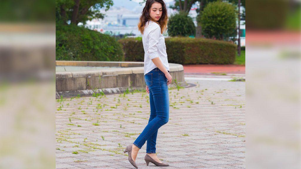 公園でボブソンジーンズを履いて立つ女性。モデル着衣写真。