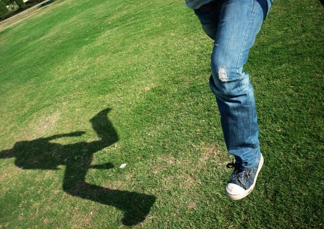 公園でジーンズを履いてジャンプする人。
