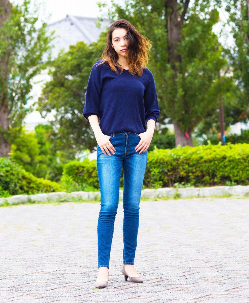 公園でボブソンのジーンズを履いてたたずむ女性。モデル着衣写真。