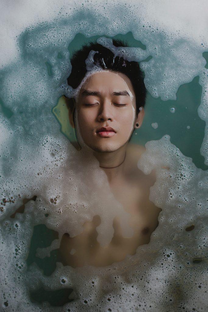 浴槽に男性が顔まで浸かって風呂に入っている写真。風呂のなかの水は青く、ところどころ泡が立っている。