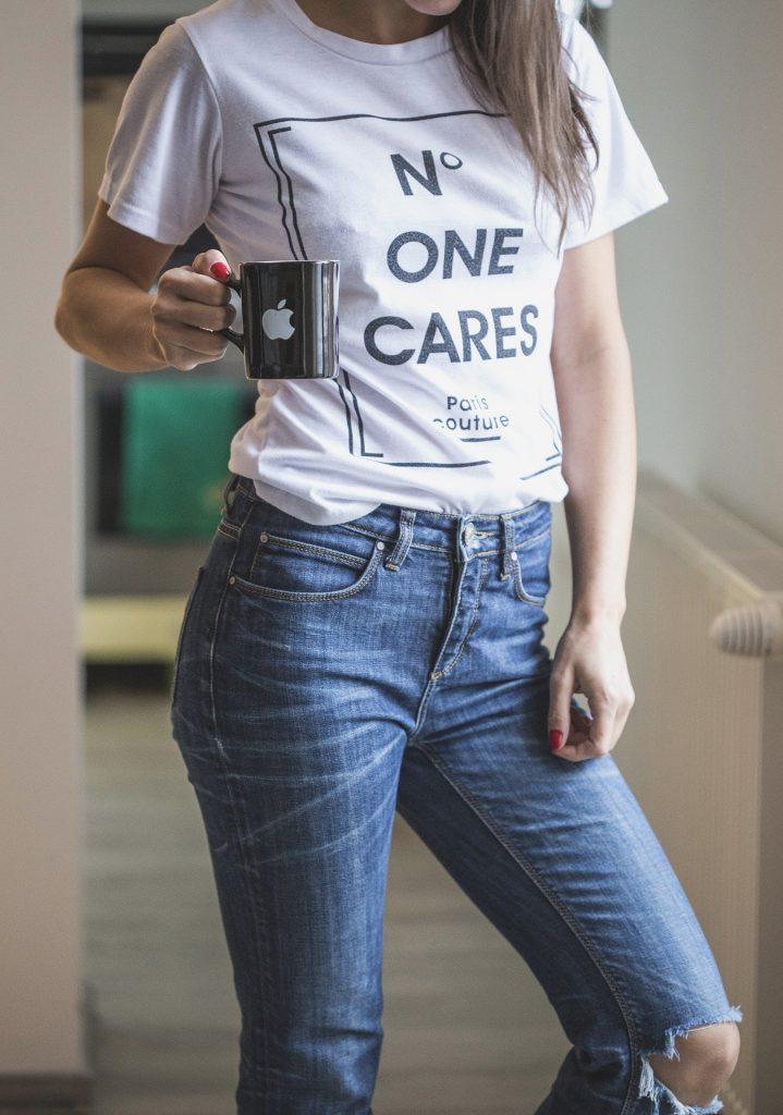 マグカップを持って立つジーンズを履いた女性。