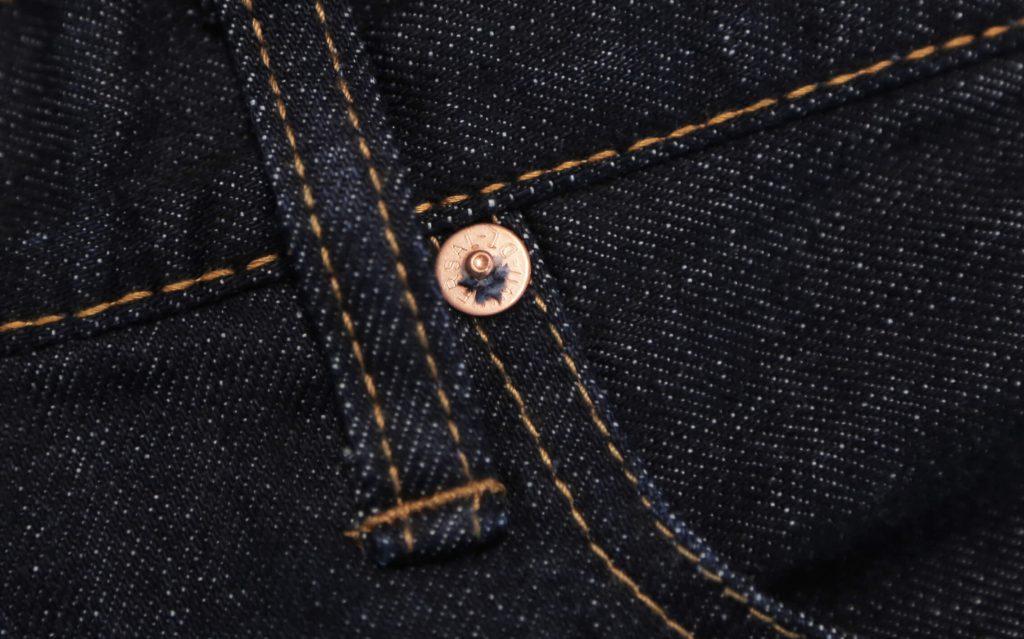 ジーンズの打ち抜きリベットのアップ画像。糸がわずかにリベットから出ている。